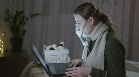 dolorido : health care, an unhealthy woman suffering from a viral infection, or cold, uses a medication using a steam inhaler and consult a doctor online using a laptop computer while sitting on couch