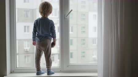 peril : dangerous situation with child at home, little boy stands on the windowsill and looking out the window with toy car in hand Stock Footage