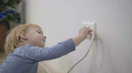 peril : child tries to insert a power plug into the electric socket close-up, a small boy dangerously playing at home