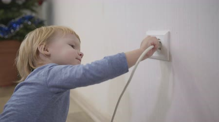 peril : child in a dangerous situation at home, little boy tries to insert a power plug into the electric socket close-up