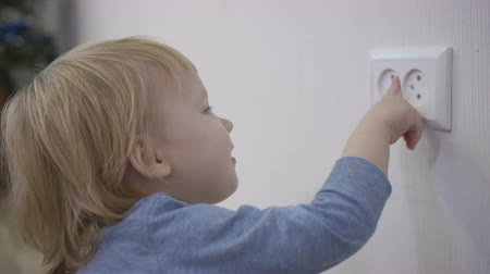 peril : curious child is in danger, small boy tries to insert a finger into the electric socket close-up at home Stock Footage