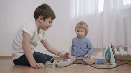 foglalat : danger to children, boy teaches little brother to turn on and off the iron in the electric socket sitting on the floor in the room