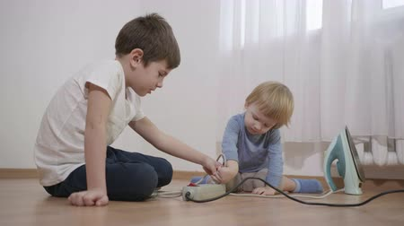 peril : dangerous games, curious little boys plugging power plug from the iron into multiple socket sitting on the floor indoors in slow motion