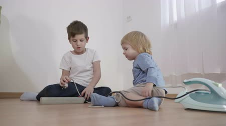 peril : kids play dangerously with electric extension cord, little boys connect wire plug from iron to socket on floor at living room