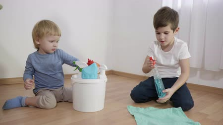 paçavra : children dangerously plays with household chemicals, little boy with a bottle sprays detergent on a rag sitting on floor next to his younger brother who throws gloves