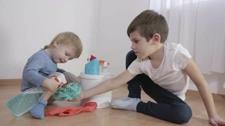paçavra : life threatening, little boy spray household chemicals from a plastic bottle on a rag held by an older brother sitting on the floor in the room