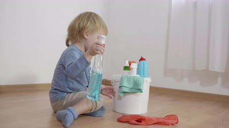 trapo : kid in danger sitting near a bucket with plastic bottles with household chemicals, little boy sprays glass detergent on rubber glove on the floor in the room