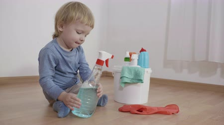 peril : child with household chemicals sitting near a bucket with plastic bottles, kid boy sprays detergent on rubber glove and dangerous play in the room