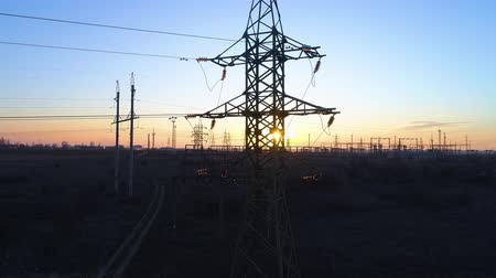 パイロン : energy efficiency, flying up the high voltage electricity tower and power lines at sunset above the field 動画素材