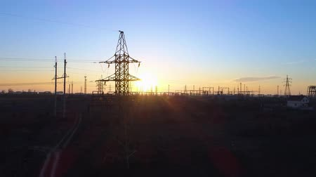transzformátor : lines of electric towers and beautiful landscape, aerial view on high voltage power pylons on field and beautiful sunset Stock mozgókép