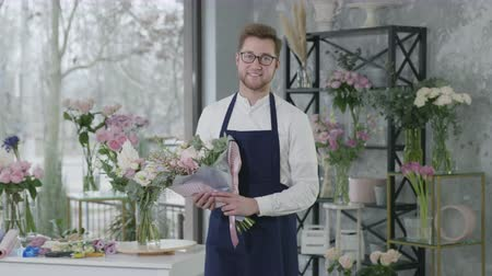 égalité hommes femmes : successful businesses, young attractive florist male representative of gender equality is standing with bouquet of flowers background of flower shop