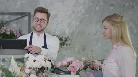 neutro : portrait of a young attractive man, representative of gender equality, works as a florist in a modern flower shop, sells a bouquet of beautiful flowers to satisfied customer who pays for her purchase in cash