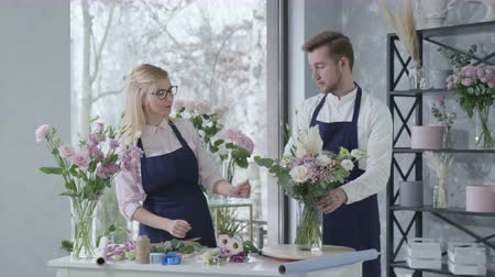 floral composition : floristry, young successful professional florists collect beautiful bouquet of fresh flowers, give five smiles and look at the camera, business success
