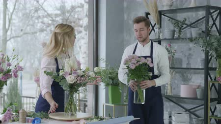 bloemenwinkel : portrait of young professionals florists owners of successful small businesses, teamwork guy and girl are smiling and looking at camera while standing in store decorated with bouquets of flowers Stockvideo