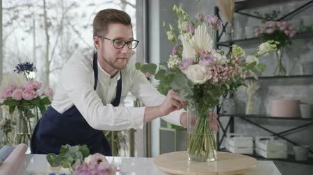 égalité hommes femmes : gender work, a professional male florist carefully collects a modern bouquet of beautiful flowers for sale in a flower shop, small business success