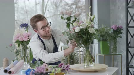 bloemenwinkel : entrepreneur male florist loving job carefully selects flower composition for sale in modern flowering shop, success small business Stockvideo