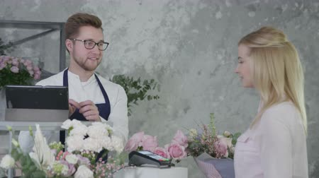 ニュートラル : portrait of young florist man, male seller sells bouquet of flowers to an blonde female buyer, woman pays purchase at modern flower shop on regular basis by contactless payment using smartphone