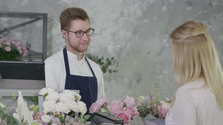 neutro : flower boutique, smiling man representative of gender equality sells modern beautiful bouquet of flowers to charming buyer, contactless payment