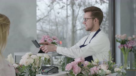 képviselő : young successful male entrepreneur, representative of gender equality works in flower shop and sells beautiful bouquet of roses, happy female buyer pays flowers in cash, small business Stock mozgókép