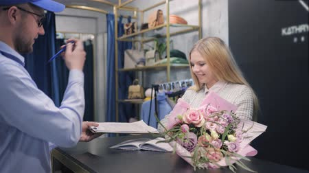 почтальон : delivery, man working in delivery service brings bouquet to client at workplace, young attractive girl receives package in form of flowers, surprise