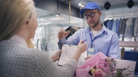 listonosz : male working in delivery service brings customer beautiful bouquet of flowers and checks order form, young attractive woman receives flowers while sitting at work