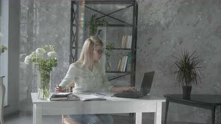 empregador : remote banking, a thin energetic woman, an entrepreneur works in an office sitting at a table with a laptop, a businesswoman uses online accounting, modern technology Stock Footage