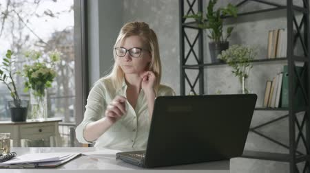 remotely : attractive blonde businesswoman working at a laptop use app online banking, a young woman working remotely at a computer rejoices at success in business, online service