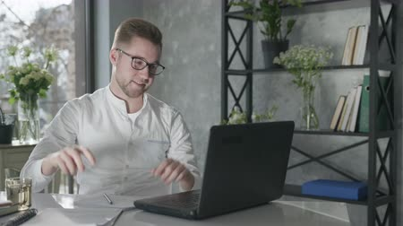 modern technologies in business, portrait of a young attractive guy in glasses for vision working at a laptop writing ideas in a notebook, distance learning Stock Footage