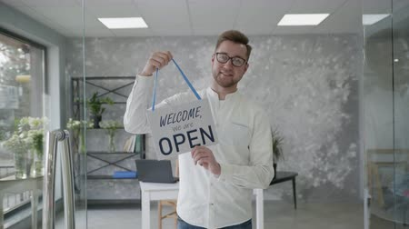 aperto cartello : small business success, attractive young entrepreneur rejoices at the opening of the store and stands with a sign open in hands Filmati Stock