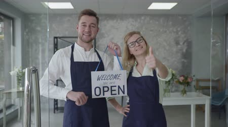opening store, young business partners male and female rejoice at opening of small business, smiling and looking at camera finger on sign Open in shop