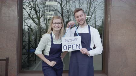 open shop, young partners rejoice at opening of small business, standing with sign Open, entrepreneurs woman and man invite to store, success