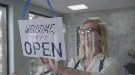 znak : small business, manager female in glasses for vision changing closed to open sign on window smiling looking outside waiting for clients, startup