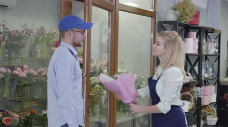 доставлять : small business, a young attractive girl working in a flower shop gives a beautiful bouquet of flowers to a man from a delivery service, a concept of success