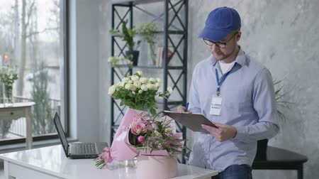 почтальон : young man checks a list of orders from an online service for the delivery of fresh bouquets of flowers from a modern flower shop, concept of success