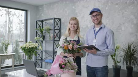 почтальон : flower delivery, portrait of young employees of a modern flower boutique preparing a list of delivery orders for beautiful bouquets of flowers, online service