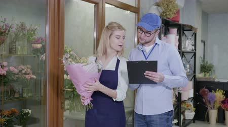 почтальон : customer care, a modern flower shop provides fast and high-quality delivery of bouquets from a flower shop, a male delivery man will check the order list in the store, small business success Стоковые видеозаписи