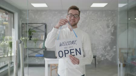 otwarcie : small businesses, portrait of a young attractive man holding a sign openly in hands, successful businessman rejoices at opening of store