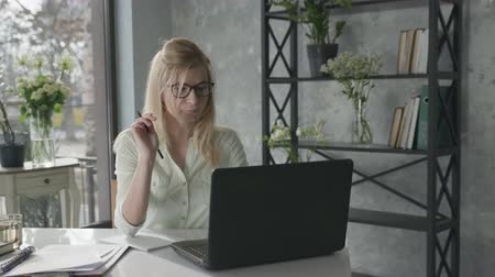 empregador : portrait of a young businesswoman, small business owners working with a laptop in an office, looking at a digital monitor and writing down creative ideas for an enterprise in a notebook Stock Footage