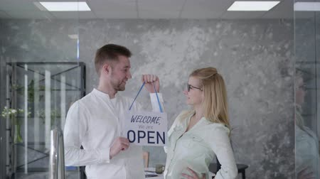 neutro : young business partners, man and woman rejoice at opening of their small business, smiling and looking at camera finger on sign Open, opening a store