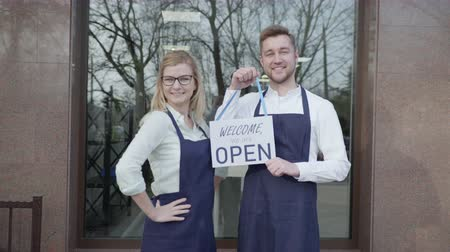 young partners rejoice at opening of success small business, entrepreneurs woman and man invite to store standing with a tablet open in hands Stock Footage
