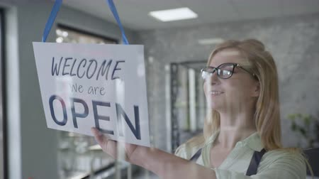 neutro : business owner an attractive woman in an apron and glasses changes the sign on front door from CLOSED to OPEN, smiling at successful opening of small business