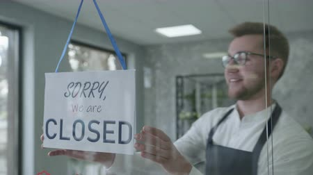 beginning of work day, male entrepreneur is changing door plate from sorry we are closed to yes we are open, business concept Stock Footage