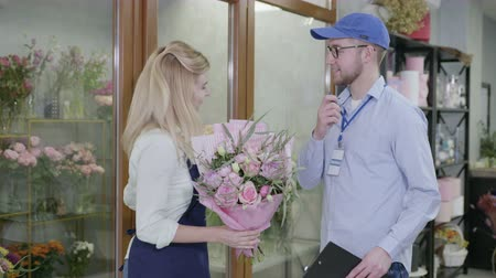 почтальон : modern flower shop provides fast and high-quality delivery of bouquets from flower shop, male delivery man will check the order list in store taking care of client Стоковые видеозаписи