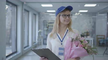 почтальон : young smiling girl with glasses and a cap works in a delivery service, a female employee delivers a bouquet of flowers to address taking care of client, small business