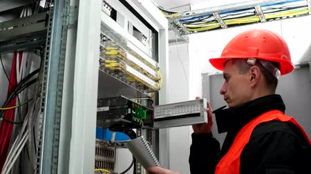 cabling : communications equipment, engineer male in a protective vest and hardhat works with server and writes notes in a notebook Stock Footage