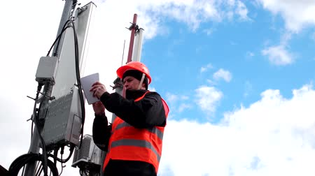 もつれた : technician working on roof near the antenna, engineer male in a protective vest and hardhat writes notes in a notebook on background of beautiful blue sky 動画素材