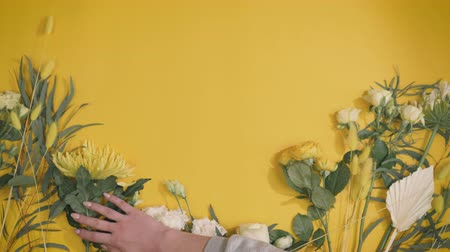 florist lays flowers on a yellow background in fast motion, beautiful composition with a place for your text