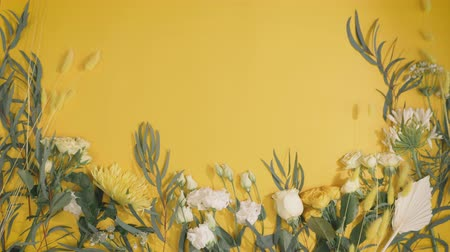 floristry, natural flowers on a yellow paper background with a place for your text Stock Footage