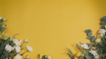 flower still life with copy space for text, florist unfold paper and puts bunch on yellow background in fast motion Stock Footage