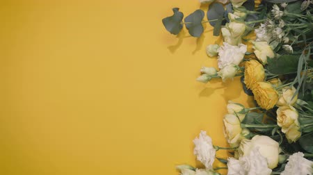 top view of beautiful fresh flowers on a yellow paper, hands of female florist deploys background for still life, vertical screen Stock Footage